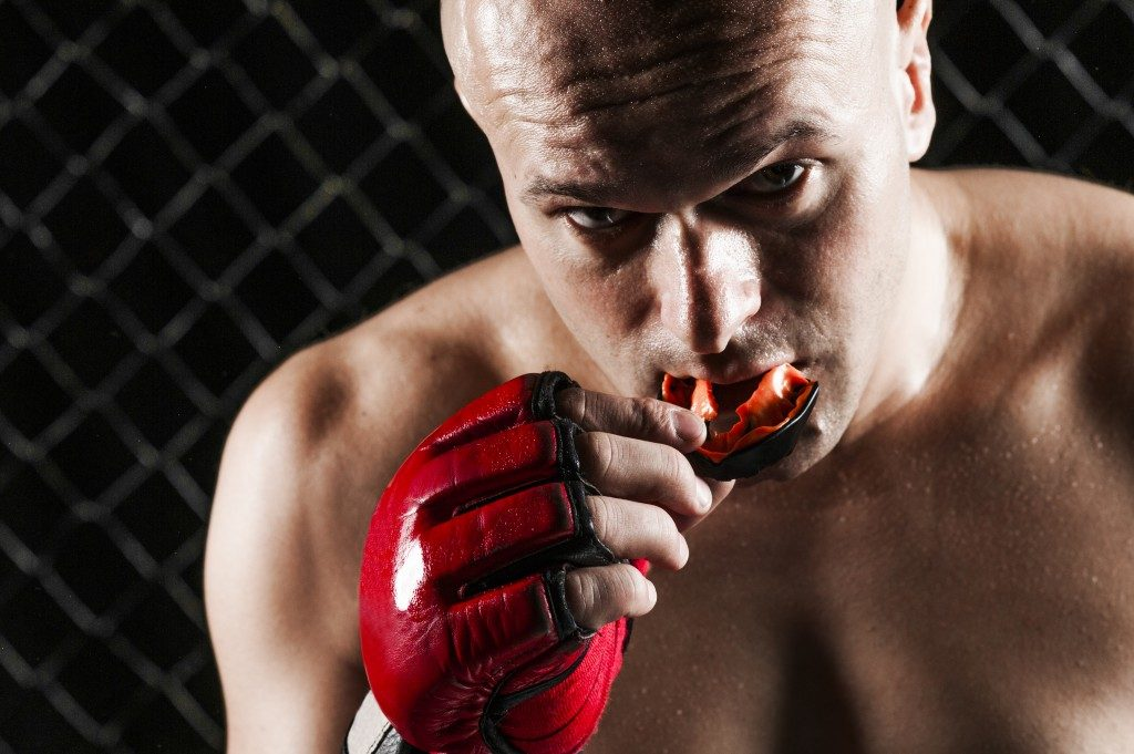 martial artist putting on mouthguard