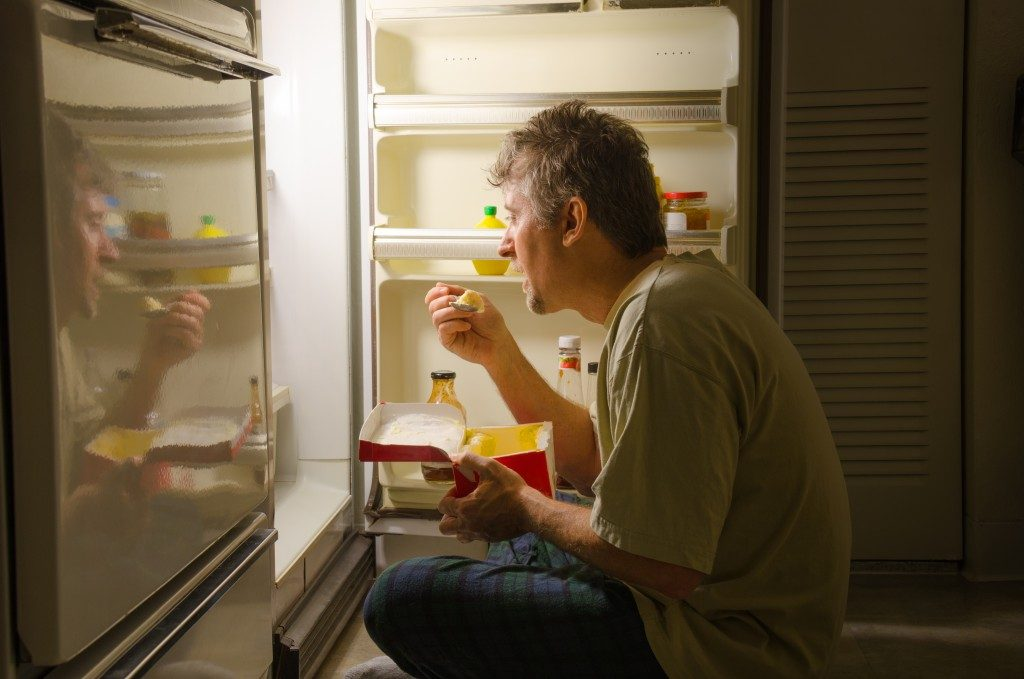 Depressed man eating in front of the fridge