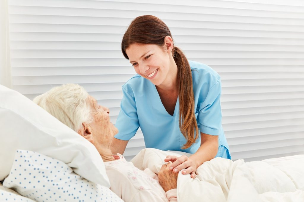 Caregiver and patient smiling at each other