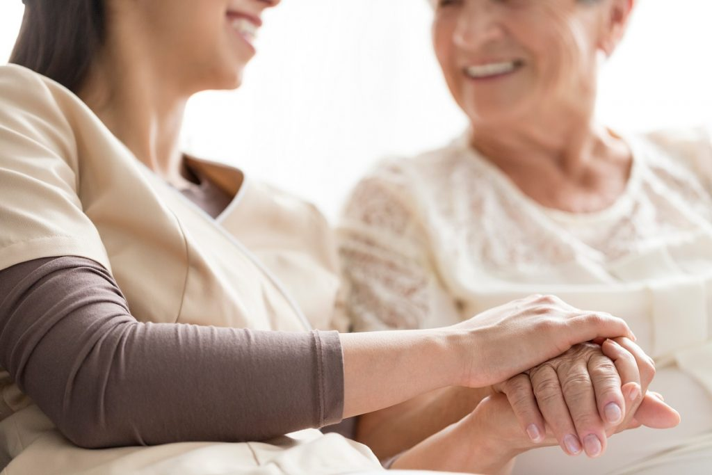 Caregiver holding the hand of her patient