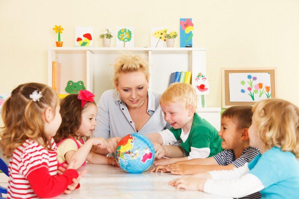 Multicultural children hands on a globe