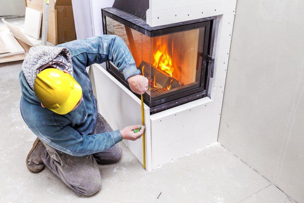 man inspecting fireplace