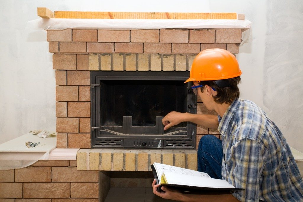 worker inspecting fireplace