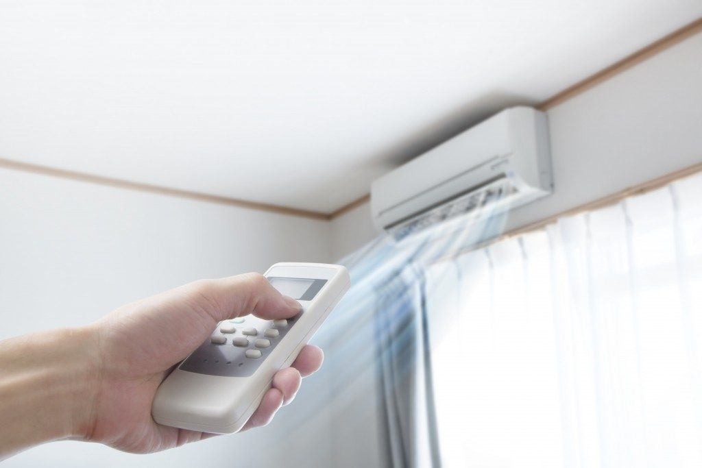 person adjusting air conditioning temperature