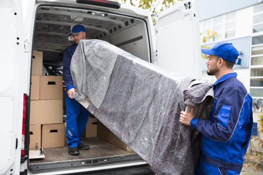 Movers unloading furniture from vehicle