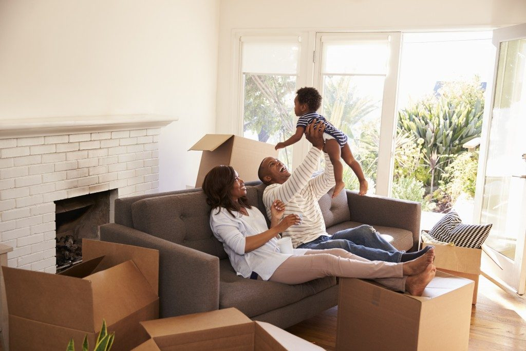family sitting in the sofa in their new home surrounded by unpacked boxes