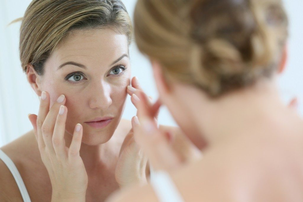 woman looking at her eyebags in the mirror
