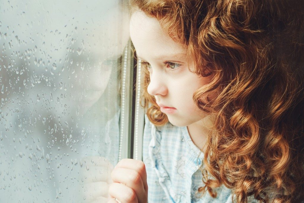 sad child looking out the window