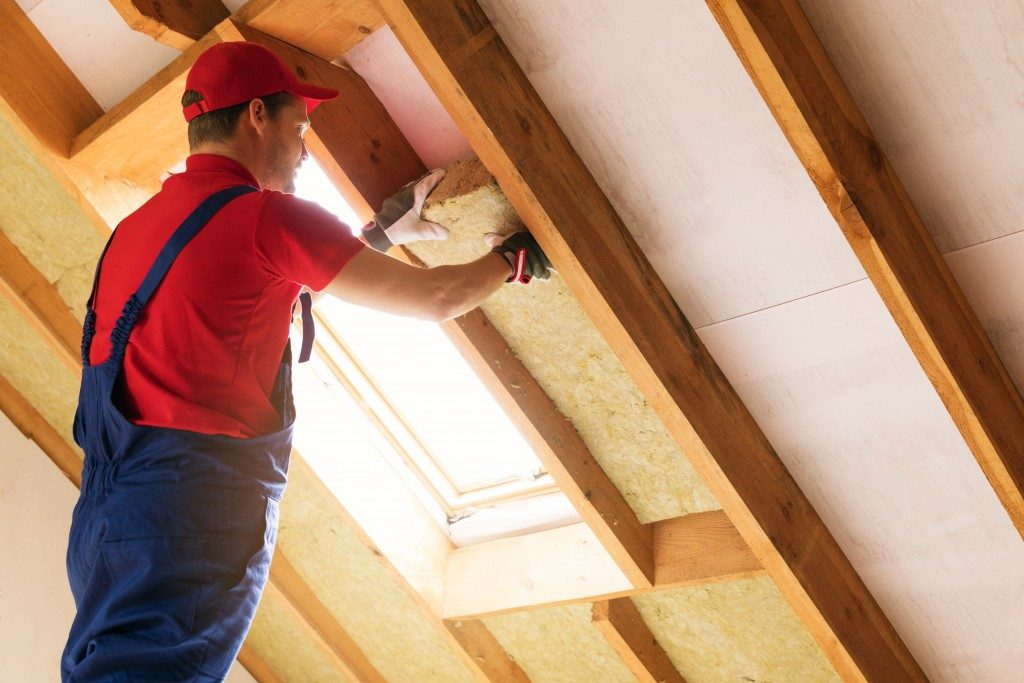 man putting insulation at the home attic