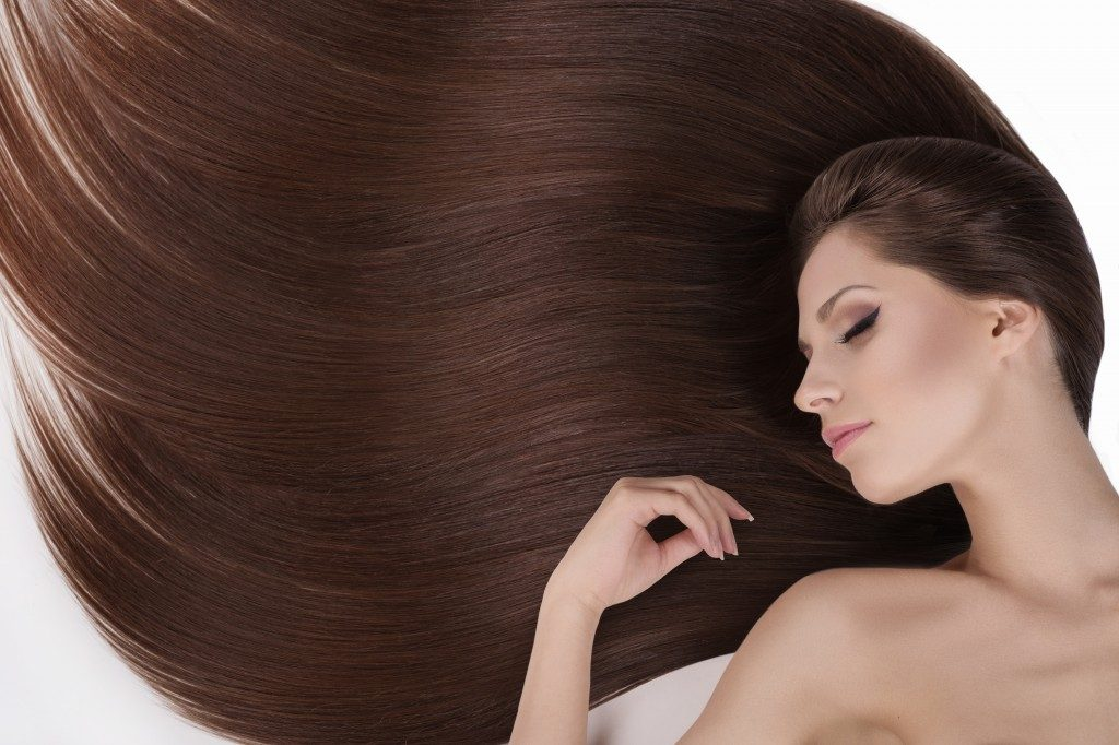 Beautiful hair. Top view of young naked women with beautiful hair keeping her eyes closed while isolated on white