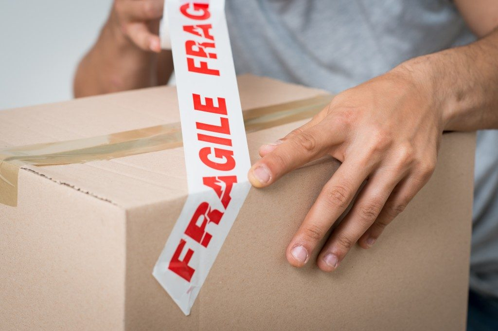 packaging box being taped with fragile warning