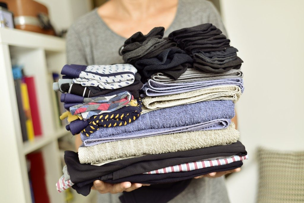 Woman carrying a pile of different folded clothes