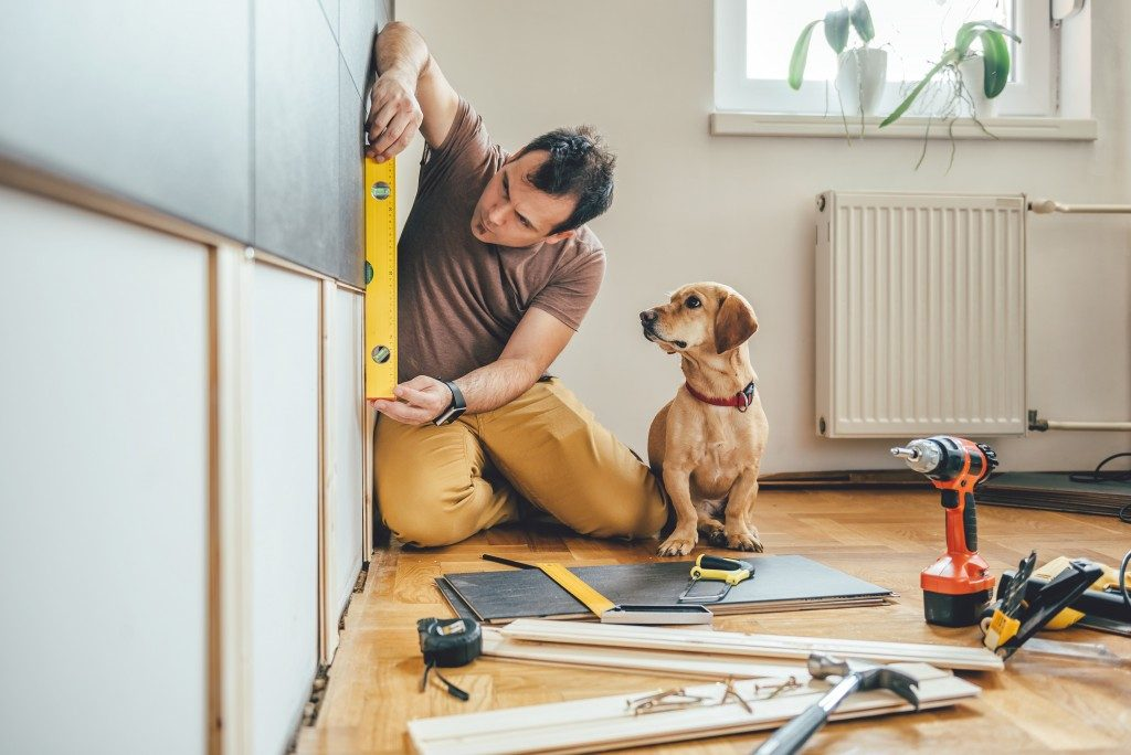 man using construction tools in improving his home