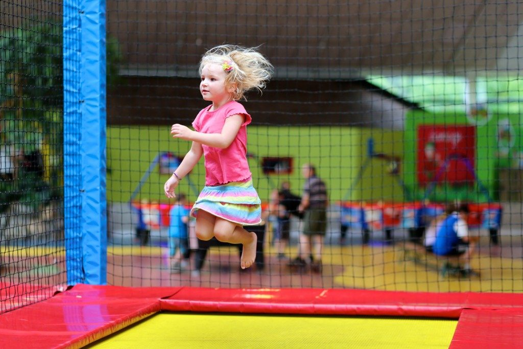 little girl jumping in a playground