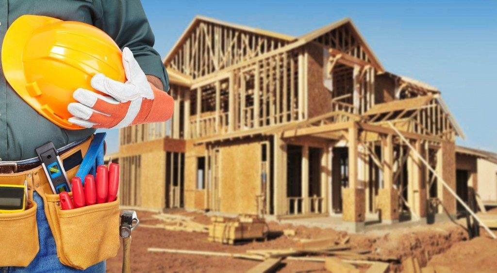 Construction worker with house construction behind