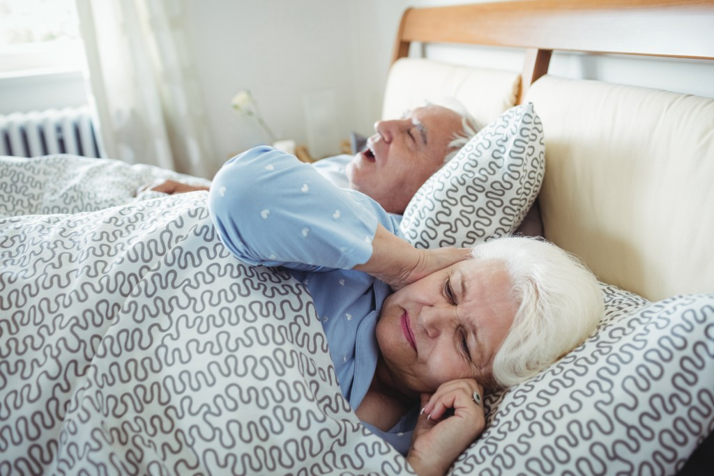 Man snoring and woman covering her ears while sleeping