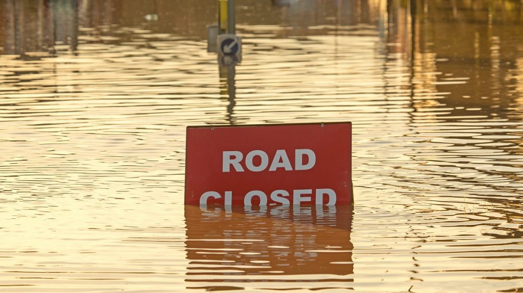 A road closed sign partially covered in flood