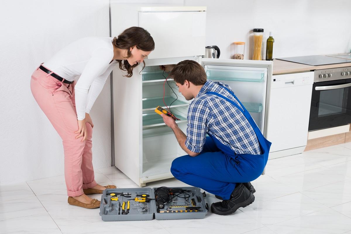 Female getting her fridge fixed