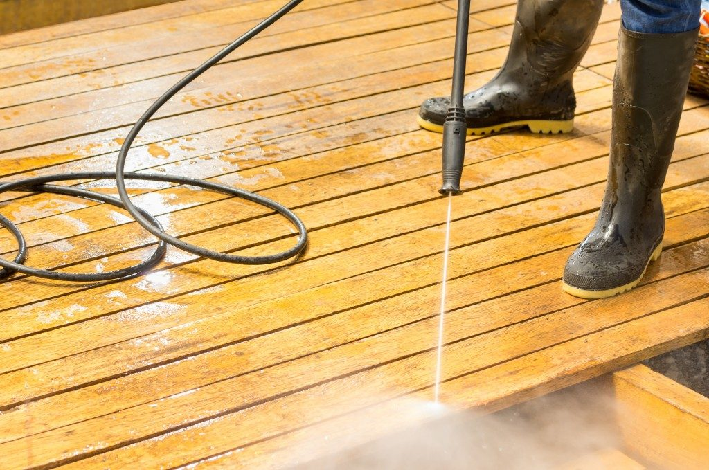 water pressure cleaner on wooden deck