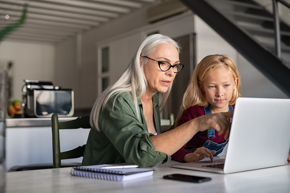 Senior woman and child studying on laptop