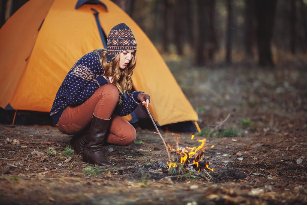 Female making fire in camping site