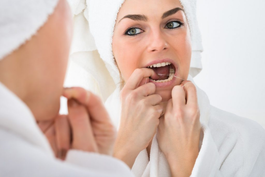 woman flossing teeth