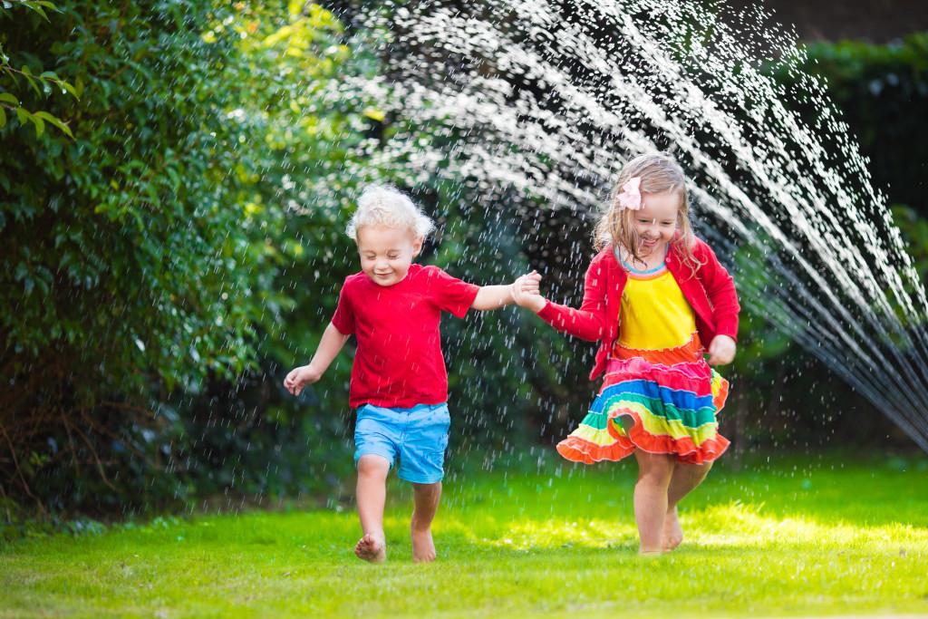 children playing with garden sprinkler