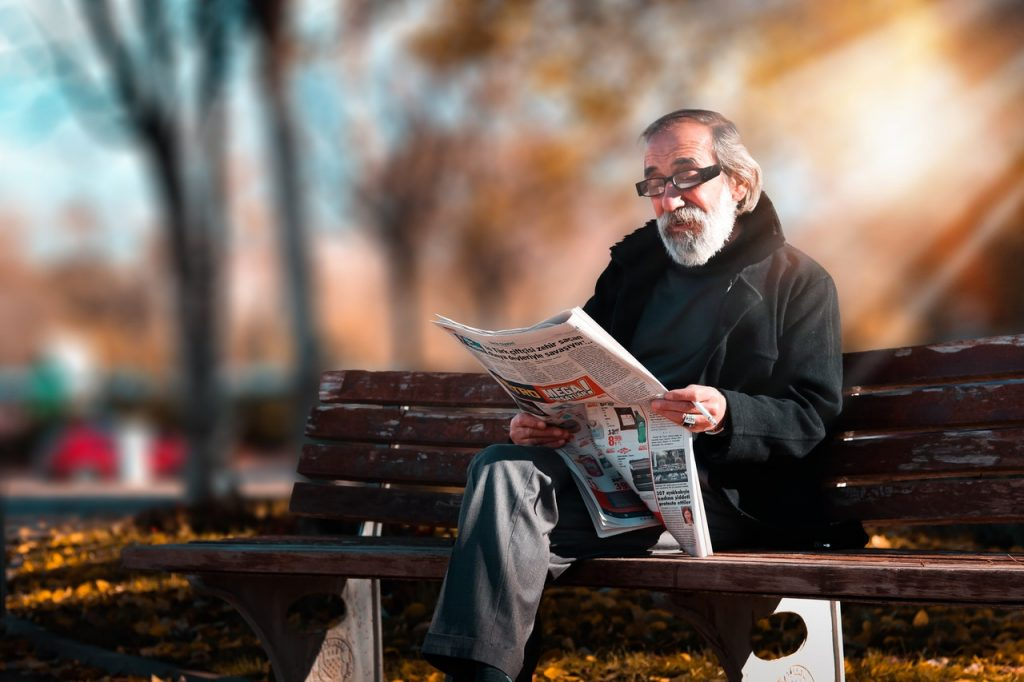 old man reading a newspaper at the park