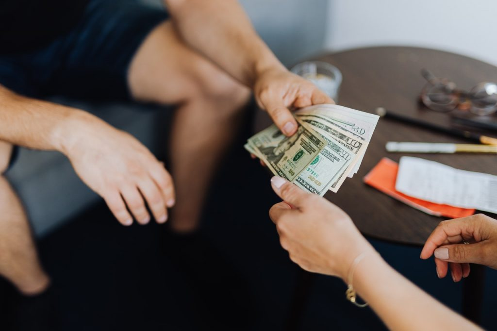 person handing over some cash to another person