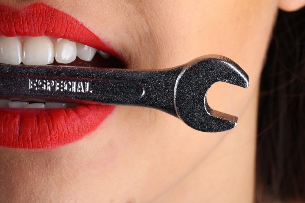 woman biting a wrench
